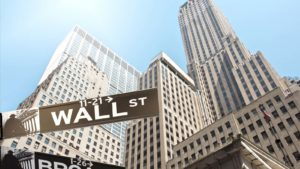 skyscraper buildings viewed from the ground with Wall Street street sign in the foreground representing pre-market stock movers.
