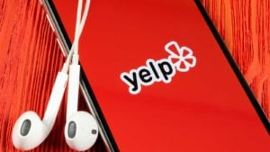yelp app on a mobile phone with headphones