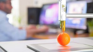 a scientist uses a 3D printer to make an orange golf ball