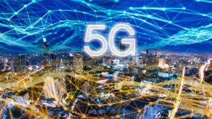 "Image of a nighttime cityscape with a hyper-connected sky and ""5G"" in white letters in the center"