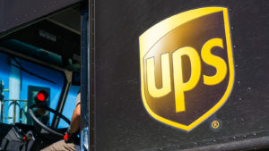 Dark brown delivery truck featuring the United Parcel Service (UPS) logo