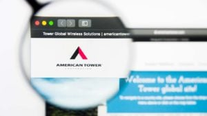 A magnifying glass zooms in on the American Tower (AMT) website.