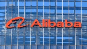 Alibaba (BABA) logo on the side of a glass-walled building. growth stocks
