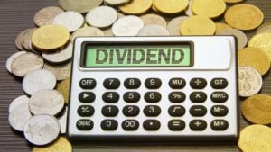 "A calculator projecting the word ""DIVIDEND"" rests on a pile of gold and silver coins."