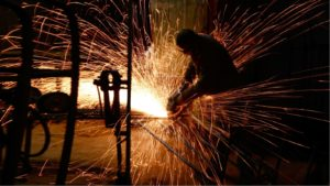 Person working on metal in the dark, with sparks flying