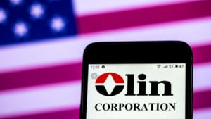Olin Corp (OLN) logo displayed on a mobile phone screen representing dividend stocks