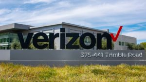 a Verizon (VZ) sign in front of headquarters building with grass in front