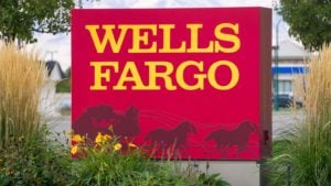 Wells Fargo (WFC) bank sign in yellow and red with wagon logo. The sign is flanked by tall grass