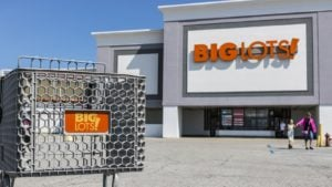 Photo of a Big Lots (BIG) store shot from the parking lot with a shopping cart in the foreground and clear blue sky in the background