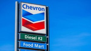 "Chevron (CVX) logo on gas station sign with ""diesel"" and ""food mart"" written underneath"