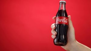 hand holding a bottle of Coca-Cola (KO) against a red background