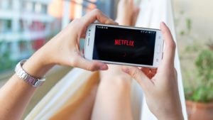 Picture of a person laying on a couch holding a mobile phone that features the Netflix (NFLX) logo on the screen