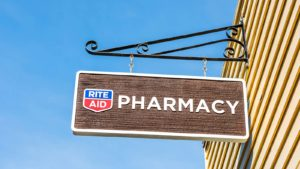 Wooden sign with Rite Aid logo and the word 'pharmacy' on it
