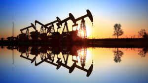 RCON stock: an oil drilling operation with a sunset in the background