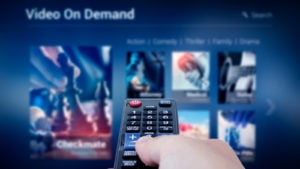 a hand pointing a remote control at a tv with a streaming service on the screen