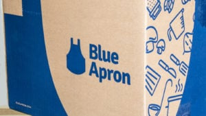 Image of the Blue Apron (APRN) logo on one of the company's branded cardboard boxes used for its deliveries. It features several images of vegetables and kitchen tools on the side, next to the logo.