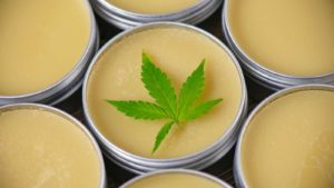 A marijuana leaf rests on top of little tins filled with a balm.