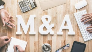 "The letters ""M&A"" on top of a wooden table surrounded by hands, a keyboard, notepad and calculator."