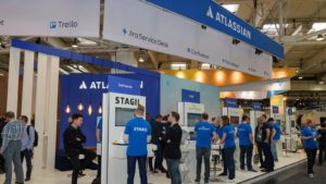 Atlassian (TEAM) employees stand at a convention booth in Hanover, Germany.