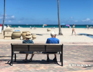 a retired couple sits on a bench at the beach