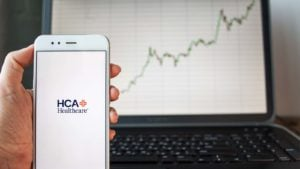 a hand holding an iPhon with an HCA logo on the screen