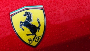 A close-up of the Ferrari logo on a red car with drops of water
