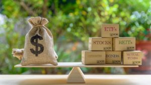 "a stock image of a bag of money on a triple beam scale, perfectly balanced with blocks labeled with asset classes such as ""REITs"" and ""ETFs"""