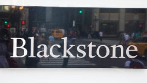 A sign for Blackstone (BX) hangs on a white wall.