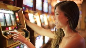 a woman smiling while using a slot machine in a casino. representing gambling stocks