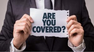 "a person holds up a scrap of paper that asks ""Are you covered?"""