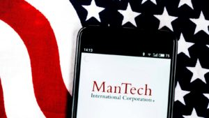 Mantech (MANT) logo displayed on a mobile phone with the American flag in the background