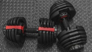 two black and red dumbbels sit on the floor