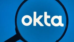A magnifying glass zooms in on the Okta (OKTA) logo.
