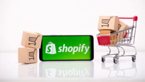 Shopify (SHOP) logo on a smartphone which is next to a miniature shopping cart and miniature cardboard boxes