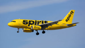 A yellow, Spirit Airlines (SAVE) branded airplane flying in the air