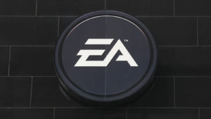 Image of Electronic Arts (EA) logo on a dark grey brick wall