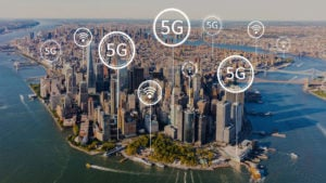 "The phrase ""5G"" in bubbles above a cityscape."
