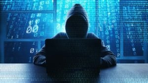 a faceless figure in a hoodie sitting in front of a laptop with lines of code in the background