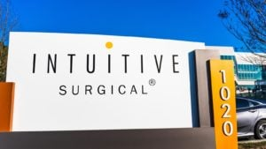 A sign with the Intuitive Surgical logo standing outside of a company office