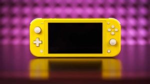 A yellow Switch Lite from Nintendo (NTDOY) sits in front of a bright pink background.