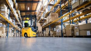Plug Stock - Image of a man driving a forklift in a warehouse.
