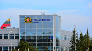 A Phillip Morris (PM) sign on a glass building.