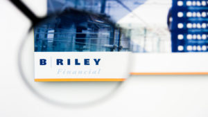 a magnifying glass enlarges the B. Riley logo on a website
