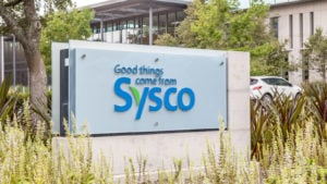 Sysco (SYY) logo on a sign with company headquarters in Houston in the background.