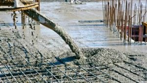 Image of wet concrete being poured onto a foundational structure