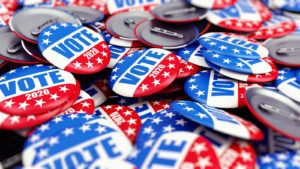 image of numerous pins with red, blue and white, stars and the words vote on them to represent 2020 election stocks