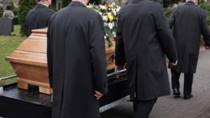 people in suits carry a casket at a funeral