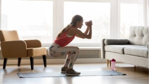 Image of a woman working out in her living room