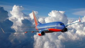 a southwest airlines (LUV) jet flying above the clouds