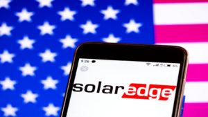 SolarEdge (SEDG) logo on phone with American flag backgroun